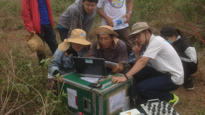 Students performing magnetic resonance sounding measurements in Cu Chi area , Saigon river banks.
